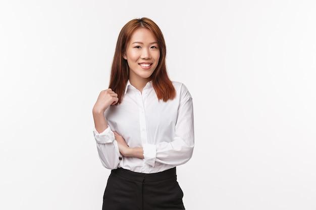 Retrato de exitosa mujer asiática feliz en camisa blanca y falda negra, tocando el mechón de cabello y sonriendo complacido, dirige su propio negocio, trabaja y sube la escalera corporativa,