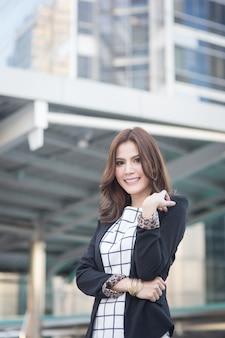 Retrato de exitosa mujer de negocios inteligente que parece confiada y sonriente