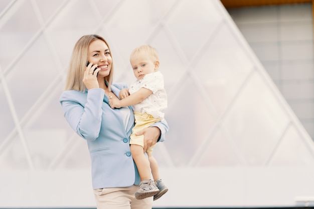 Retrato de una exitosa mujer de negocios en traje azul con bebé