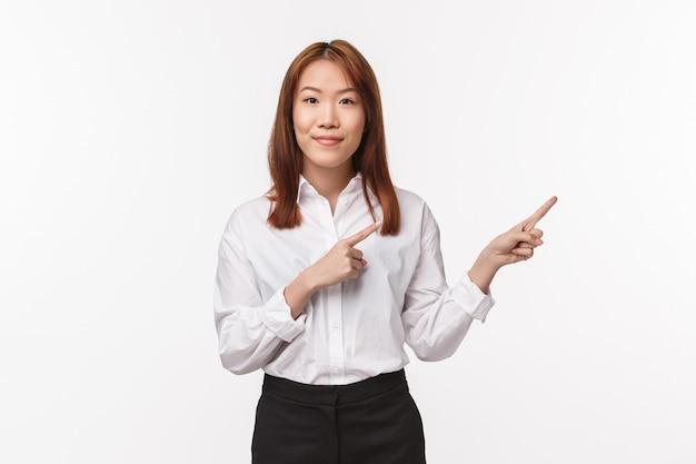 Retrato de exitosa tutora bastante asiática, empresaria emprendedora señalando con el dedo a la derecha y sonriendo agradable a la cámara mientras habla sobre las características del producto, publicidad,