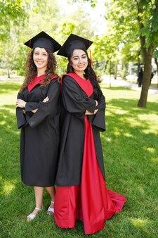 Retrato de exitosas estudiantes de posgrado con gorra al aire libre cerca de la universidad