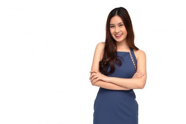 Retrato de exitosas mujeres asiáticas de negocios en vestido azul con los brazos cruzados y una sonrisa aislada sobre la pared blanca, joven empresaria sonriendo y mirando a cámara, concepto de sentimiento feliz