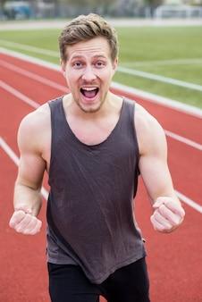 Retrato de exitoso corredor masculino con puño cerrado