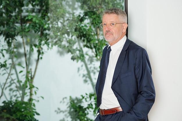 Retrato de exitoso empresario senior en vasos apoyado en la pared