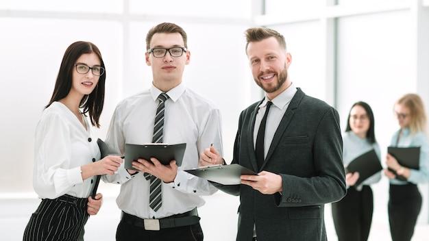 Retrato de un exitoso equipo de negocios de pie en el vestíbulo de la oficina.