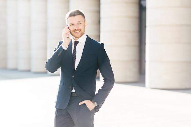 Retrato de un exitoso gerente masculino satisfecho con las tarifas móviles, hace una llamada telefónica