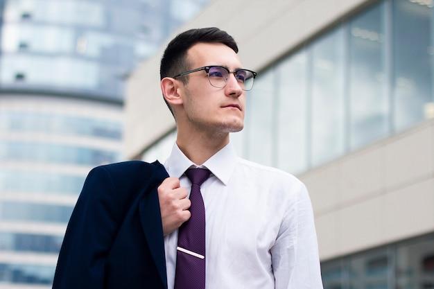 Retrato de un exitoso hombre de negocios confía en gafas y traje al aire libre.