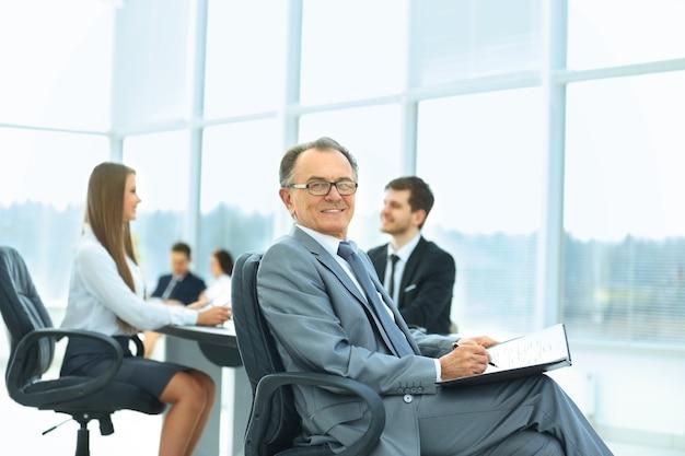 Retrato de un exitoso hombre de negocios en la oficina en el fondo del equipo empresarial