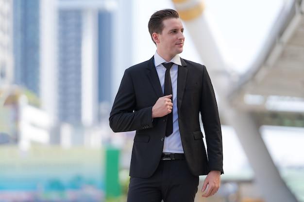 Retrato de exitoso hombre de negocios de pie frente a modernos edificios de oficinas