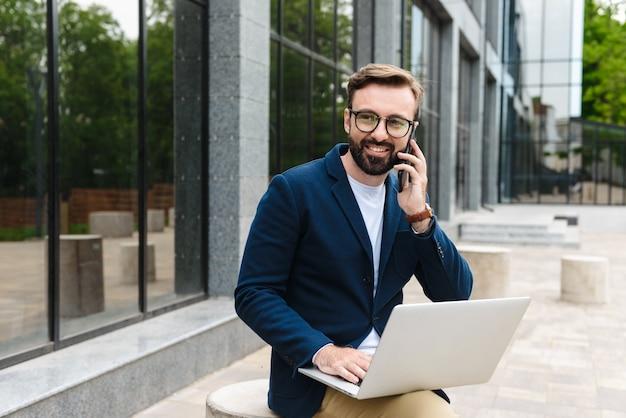 Retrato de exitoso hombre de negocios usando anteojos hablando por teléfono celular y usando la computadora portátil mientras está sentado al aire libre cerca del edificio