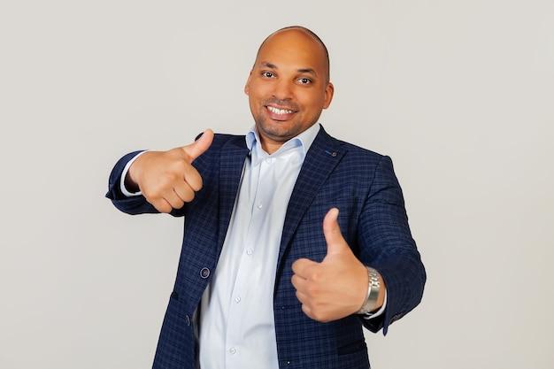 Retrato de un exitoso joven empresario afroamericano haciendo un gesto positivo con la mano con aprobación, sonriendo con los pulgares hacia arriba y feliz por el éxito. gesto del ganador. de pie sobre una pared gris.