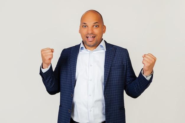 Retrato de un exitoso joven empresario afroamericano, muy feliz y emocionado, haciendo un gesto de ganador con las manos levantadas, sonriendo y gritando éxito. concepto de celebración.