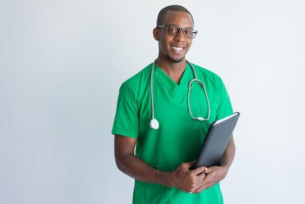 Retrato de exitoso joven médico con carpeta y estetoscopio.