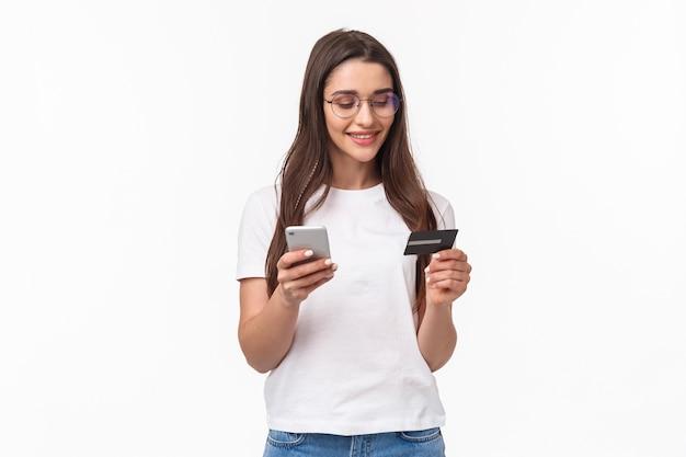 Retrato, expresivo, mujer joven, con, móvil, y, tarjeta de crédito