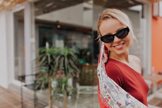 Retrato exterior de adorable dama rubia feliz con gafas de sol y mantón