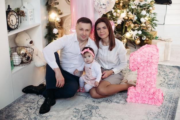 Retrato de familia con adorable niña posando sobre una alfombra contra el árbol de navidad decorado