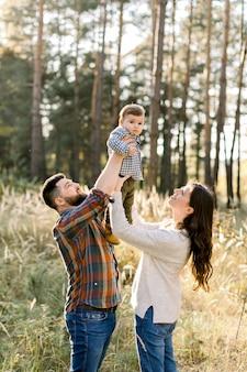 Retrato de familia al aire libre de padres jóvenes felices, vistiendo ropa casual elegante, divirtiéndose y levantando a su pequeño y lindo hijo, durante la caminata en el bosque de otoño en un día soleado