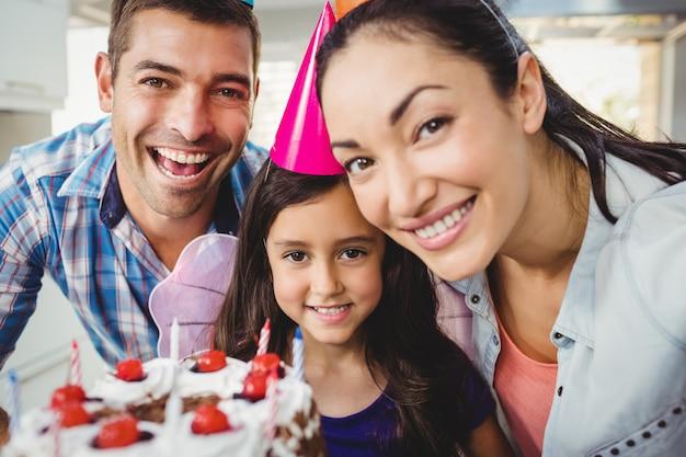 Retrato de familia alegre celebrando cumpleaños en casa