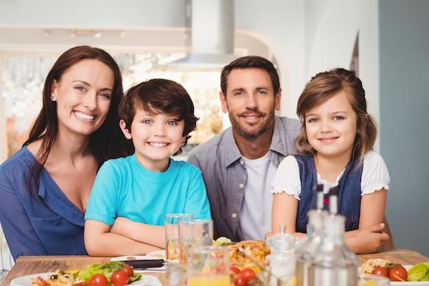 Retrato de familia alegre con comida en la mesa de comedor