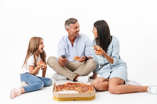 Retrato de una familia alegre comiendo pizza