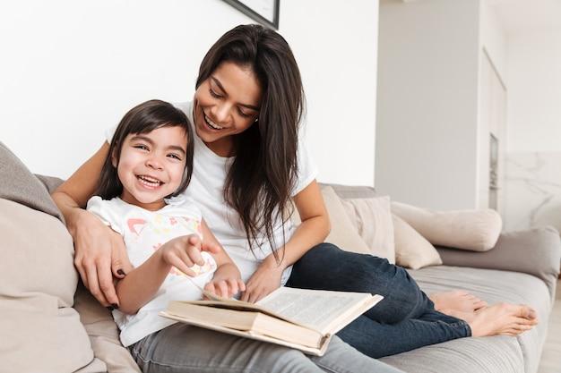 Retrato de familia alegre madre e hijo pasar tiempo juntos, sentados en el sofá en la sala de estar y leer el libro