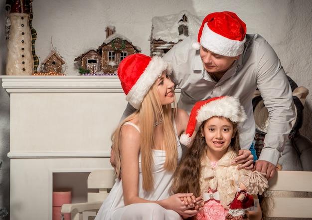 Retrato de familia amigable mirando a la cámara en la noche de navidad