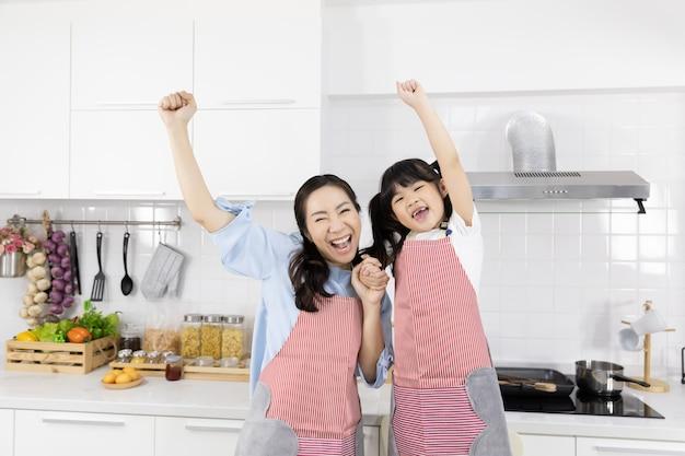 Retrato de familia asiática vistiendo delantales en la cocina
