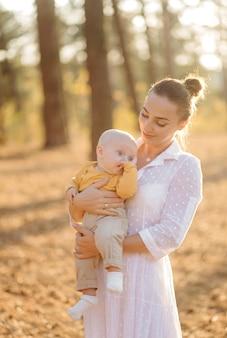Retrato de familia atractiva joven con hijo pequeño, posando en el hermoso bosque de pinos de otoño en un día soleado. hombre guapo y su bella esposa morena