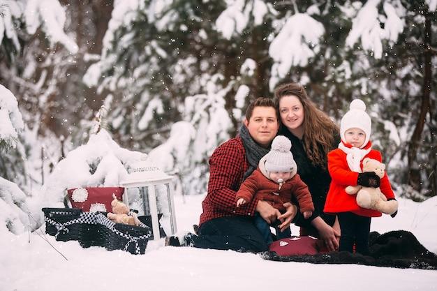 Retrato de una familia elegante pasar un buen rato en el bosque de invierno.