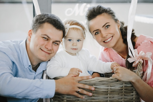 Retrato de familia encantadora con su pequeña hija linda