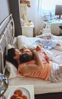Retrato de familia feliz abrazando acostado sobre la cama en una mañana relajada. concepto de tiempo de ocio familiar de fin de semana.