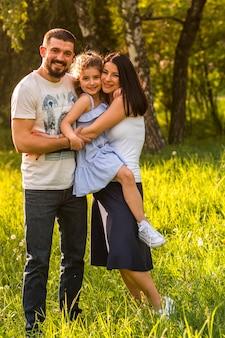 Retrato de una familia feliz abrazando en el parque