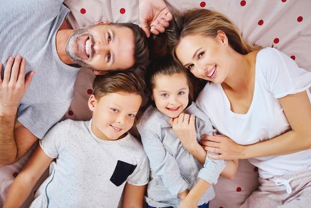 Retrato de familia feliz acostado en la cama