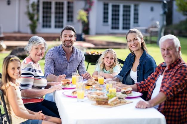 Retrato de familia feliz almorzando en el jardín