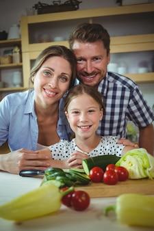 Retrato de familia feliz apoyándose en la encimera de la cocina