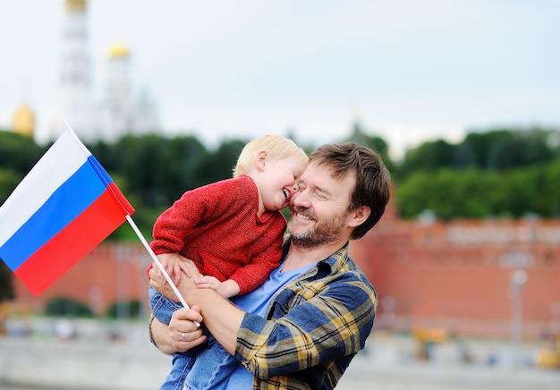 Retrato de familia feliz con la bandera rusa con el kremlin de moscú