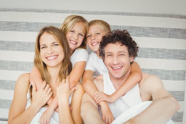 Retrato de familia feliz en la cama