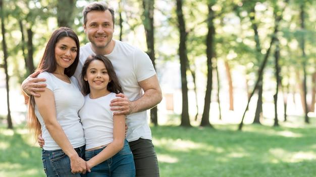 Retrato de familia feliz en camiseta blanca de pie juntos en el parque