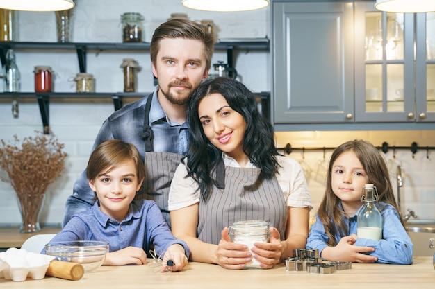 Retrato de una familia feliz cocinando galletas en la cocina