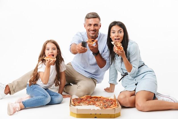 Retrato de una familia feliz comiendo pizza
