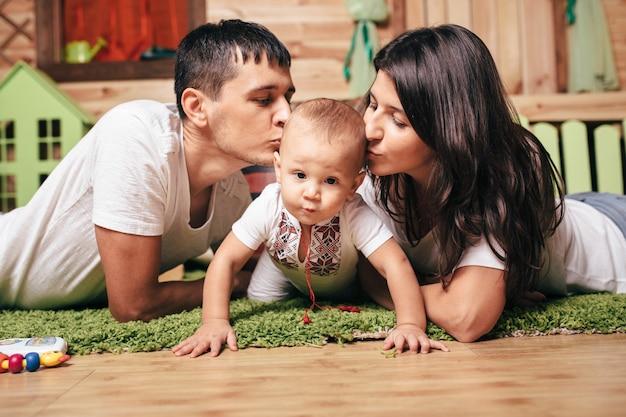 Retrato de familia feliz, concepto de amor de unas vacaciones en familia. mamá, papá besando al niño en casa en el piso. emociones de felicidad. día de la mujer. día de la madre, día del padre.