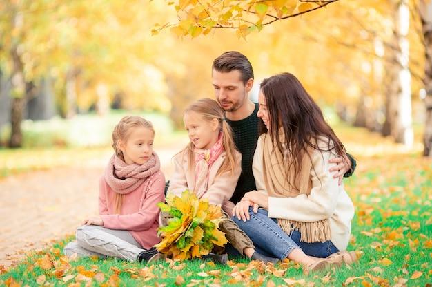 Retrato de familia feliz de cuatro en día de otoño