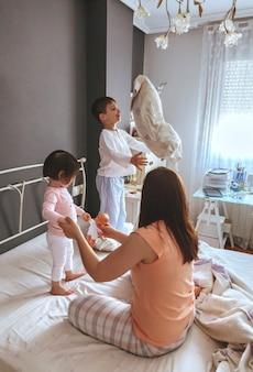Retrato de familia feliz jugando sobre la cama en una mañana relajada. concepto de tiempo de ocio familiar de fin de semana.