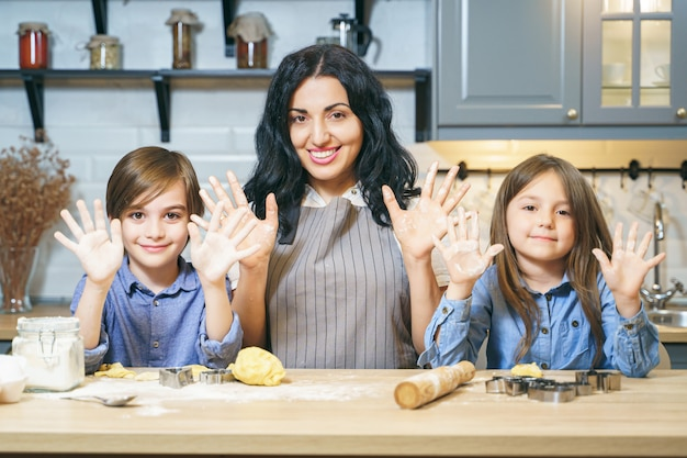 Retrato de una familia feliz de mamá y dos niños mostrando las manos y sonriendo mientras hacen galletas en la cocina