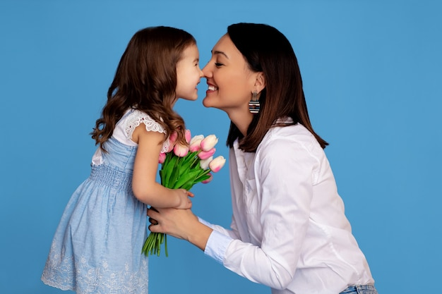 Retrato de una familia feliz. mamá e hija se miran y sostienen un ramo de tulipanes rosados
