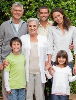 Retrato de una familia feliz mirando a la cámara en el jardín