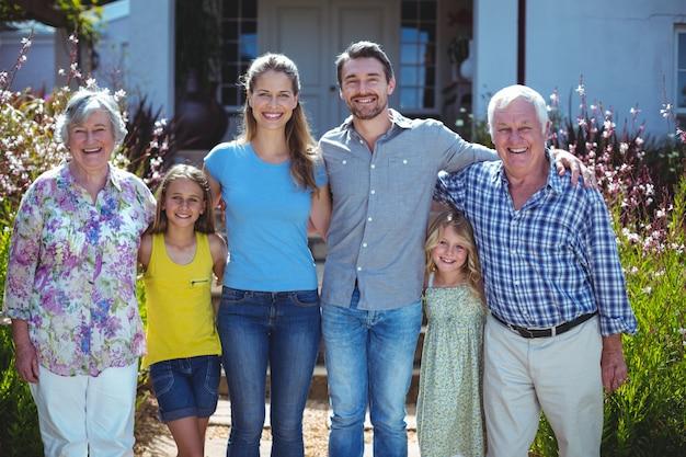 Retrato de familia feliz multigeneración contra casa
