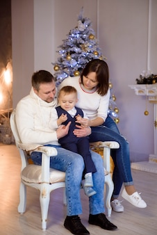 Retrato de familia feliz en navidad, madre, padre e hijo en casa.