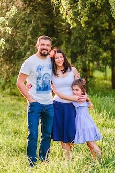 Retrato de familia feliz parado juntos en el parque
