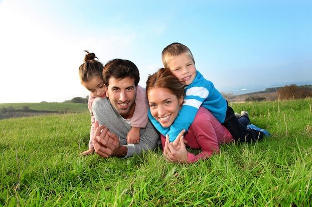 Retrato de la familia feliz que pone en campo del país